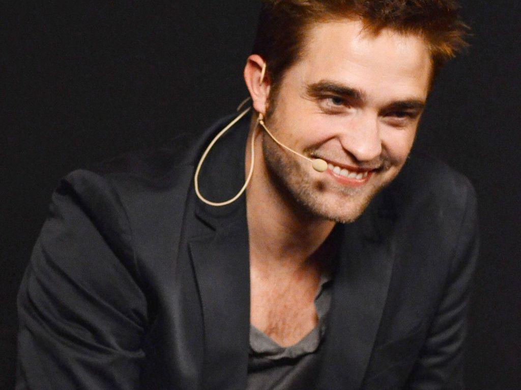 Robert Pattinson neigt sich grinsend nach vorne