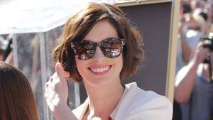 Anne Hathaway strahlt mit Sonnenbrille auf der Nase