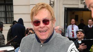 Elton John in Collegejacke lacht