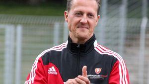 Michael Schumacher lächelt im roten Trikot