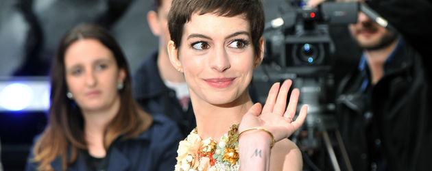 Anne Hathaway winkt glücklich bei der Europapremiere von Batman in London