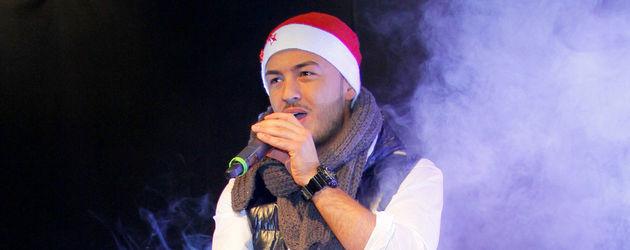 Ardian Bujupi auf der Bühne mit Weihnachtsmütze