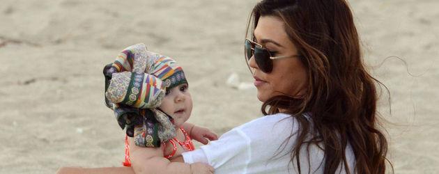 Kourtney Kardashian und ihre Tochter sitzen im Sand