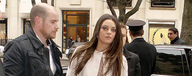 Mila Kunis im weißen Mantel und gehend