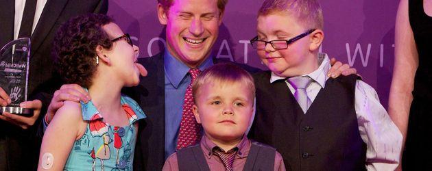 Prinz Harry umringt von fröhlichen Kindern