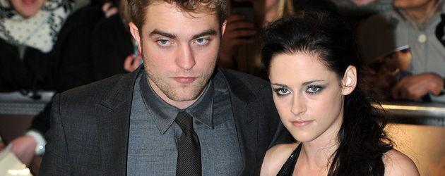 Robert Pattinson im schwarzen Anzug und Kristen im schwarzen Kleid