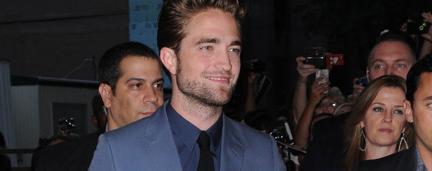 Robert Pattinson lächelt im blauen Anzug