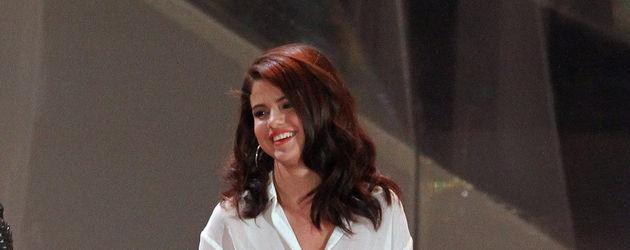 Selena Gomez trägt Schuhe in der Hand