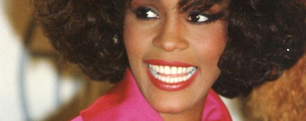 Whitney Houston lächelt im pinken Oberteil