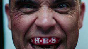 Robbie mit Mundschutz, auf dem die Abkürzung seines Albums zu lesen ist