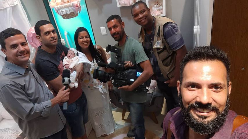 Rodrigo Kunstmann zusammen mit Grumpy Baby Isabela, ihren Eltern und einem Fernsehteam