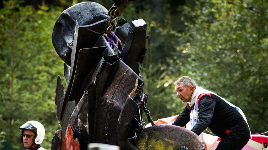 Ein Streckenposten mit dem zertrümmerten Rennwagen von Anthoine Hubert