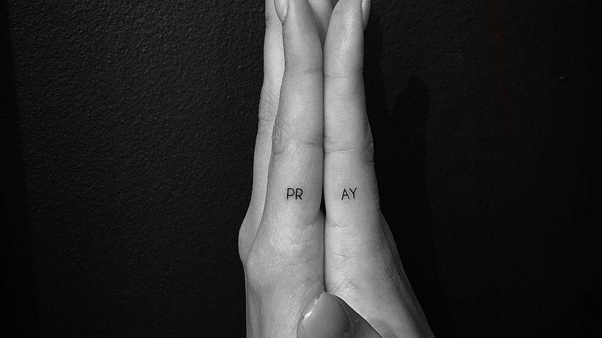 """Hailey Biebers Hände mit dem tätowierten Wort """"pray"""", Juni 2016"""
