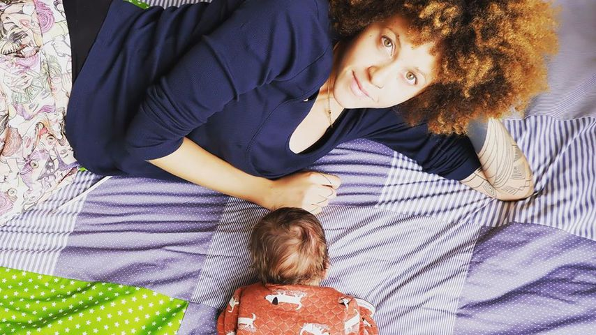 Joy Lee Juana Abiola-Müller auf einer Kuscheldecke mit Sohn Lovis